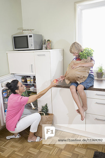 Woman giving an apple to her son at refrigerator