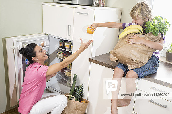 Boy giving an orange to his mother at refrigerator