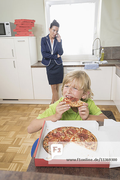 Boy eating pizza while mother has business call in kitchen