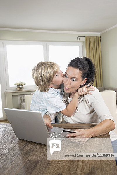 Boy kissing his mother while she online shopping on laptop