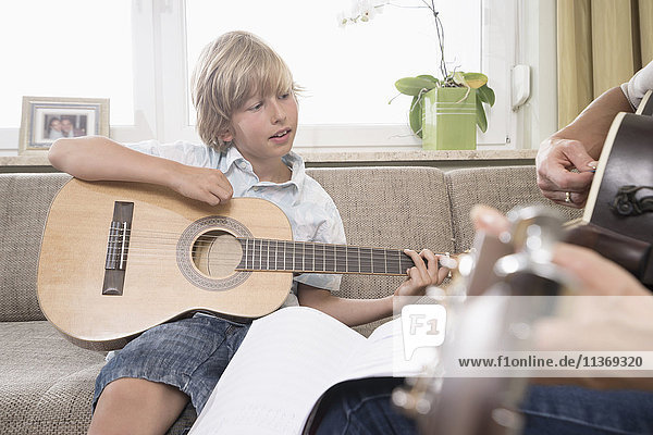 Woman with her son playing guitar in living room