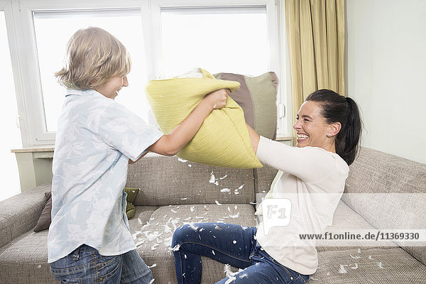 Woman pillow fighting with her son in living room