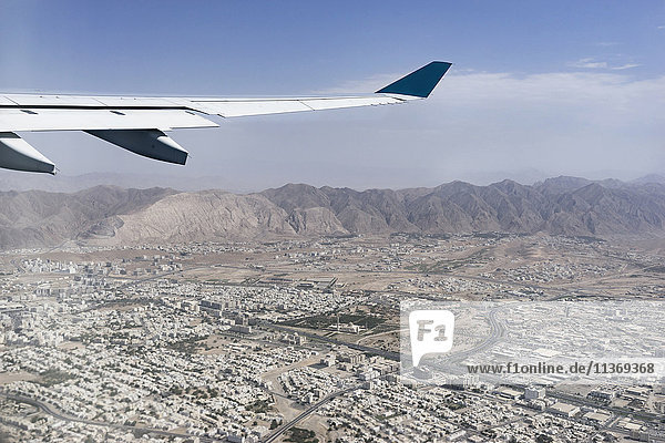 Cropped image of airplane flying above city  Maskat  Oman Cropped image of airplane flying above city, Maskat, Oman