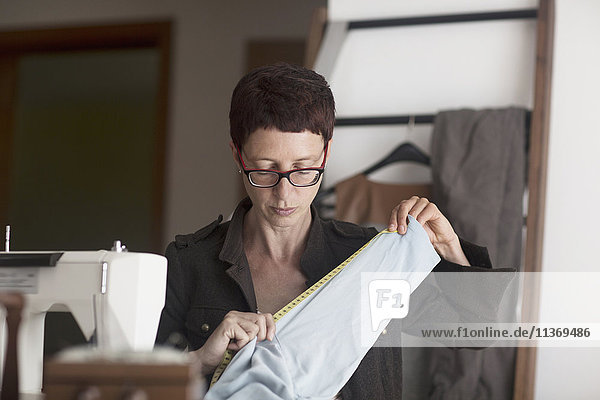 Female dressmaker measuring fabric next to sewing machine Female dressmaker measuring fabric next to sewing machine