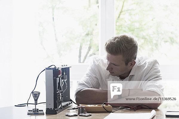 Engineer repairing CD player in workshop