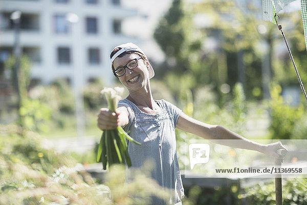 Happy mature woman working in urban garden
