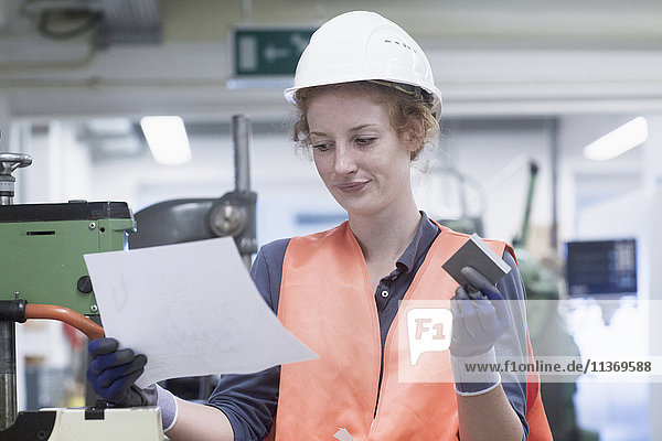 Young female engineer holding machine part with paper in an industrial plant
