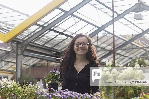 Happy young woman in greenhouse