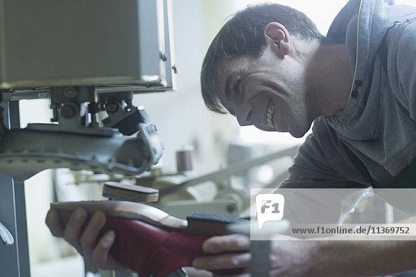 Shoemaker repairing shoe in a workshop