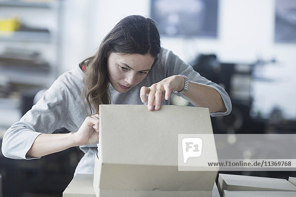 Print worker packaging cardboard box in an industry