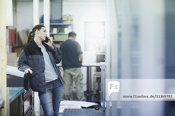Print worker talking on mobile phone in an industry