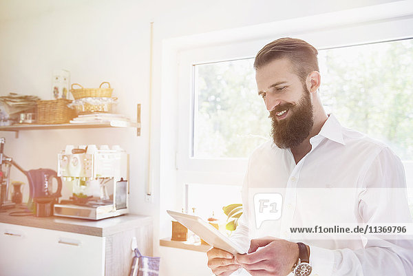 Young man using digital tablet in the kitchen