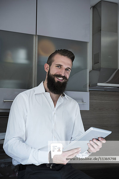 Portrait of a young man using digital tablet in the kitchen