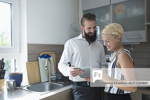 Young couple using digital tablet in the kitchen