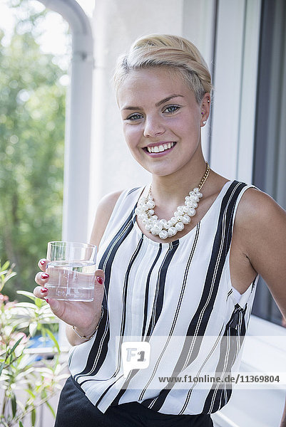 Portrait of a young woman drinking water on the balcony and smiling