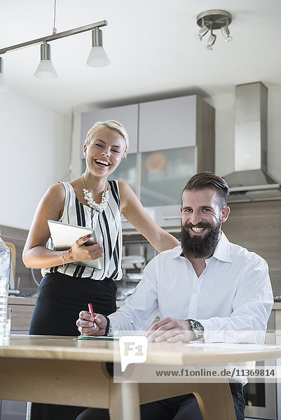 Portrait of a young couple with digital tablet in the kitchen and smiling