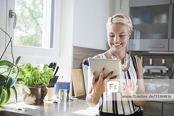 Young woman using digital tablet in the kitchen