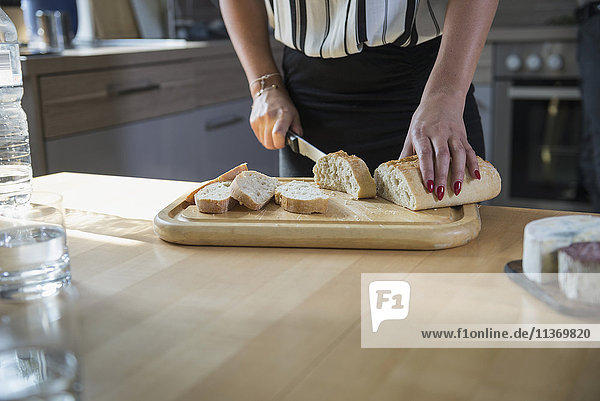 Close-up of young woman cutting slices of bread in the kitchen
