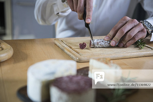 Mid section of a man cutting salami in the kitchen