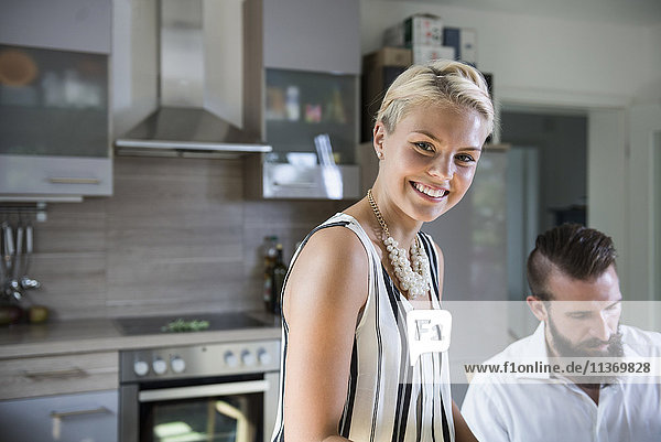 Portrait of a young woman in the kitchen and man in the background