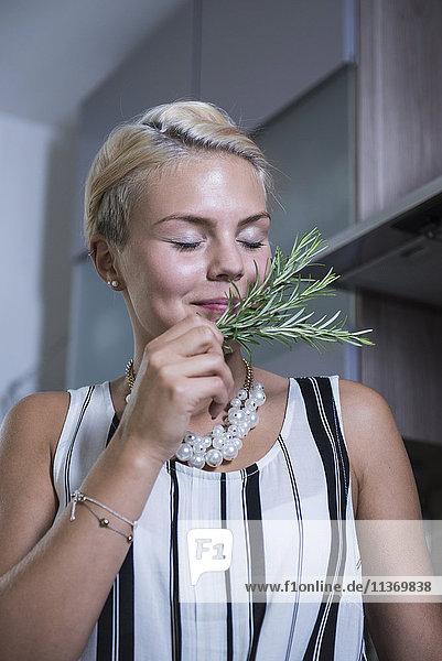 Young woman smelling rosemary in the kitchen