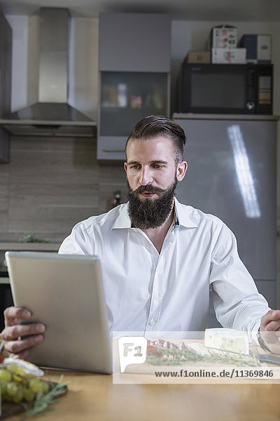 Young man looking recipe on digital tablet for meal in the kitchen