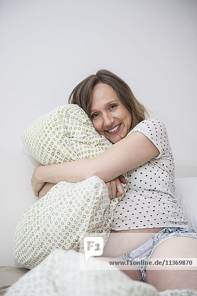 Happy pregnant woman cuddling her pillow in bed