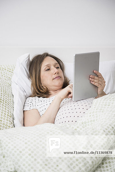 Pregnant woman lying in bed and using digital tablet