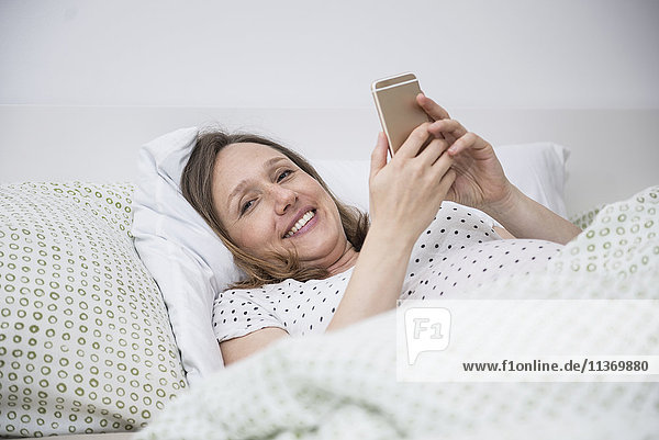 Pregnant woman lying in bed and using on mobile phone