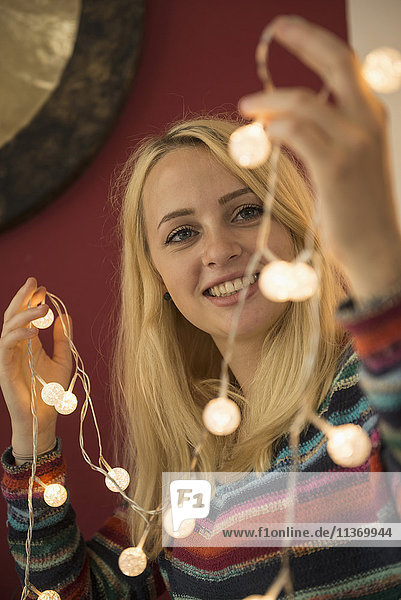 Young woman looking at fairy lights in the living room