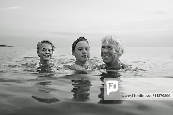 Grandmother swimming with granddaughters