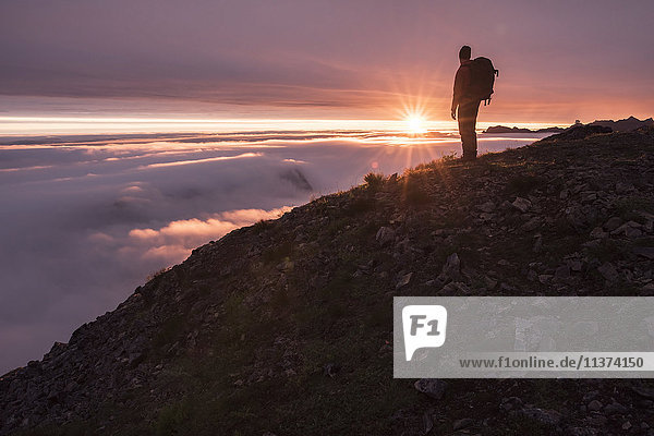 Hiker in mountains at sunset