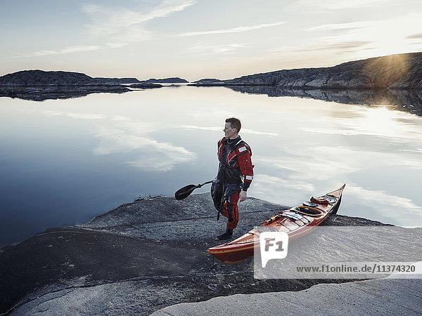 Man with kayak on rocky coast