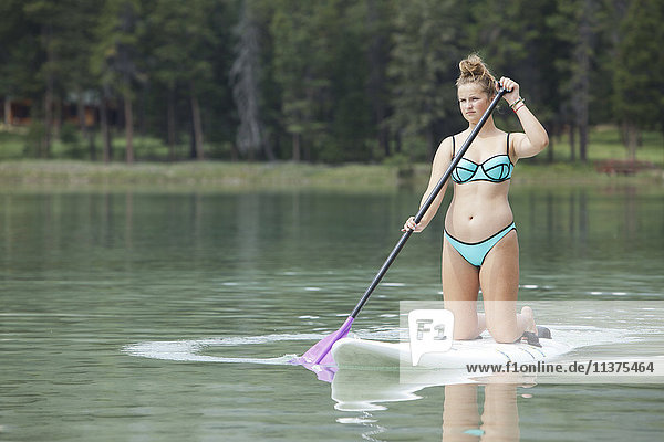 Caucasian girl paddleboarding on lake