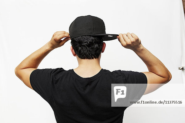 Rear view of Hispanic man adjusting baseball cap