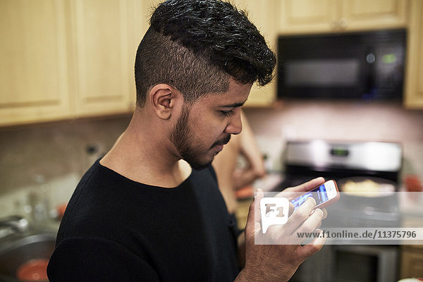 Middle Eastern man texting on cell phone in kitchen