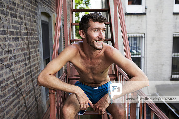 Caucasian man sitting on urban fire escape