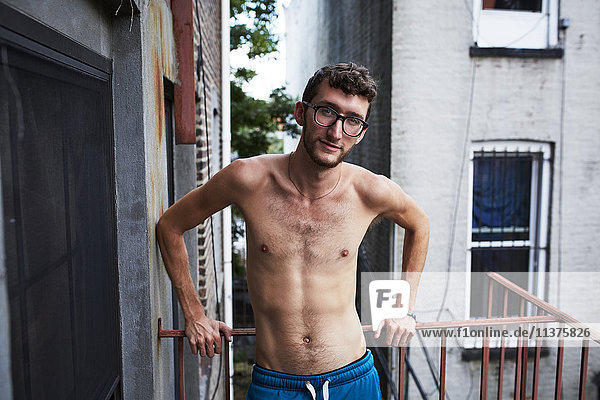 Caucasian man standing on urban fire escape