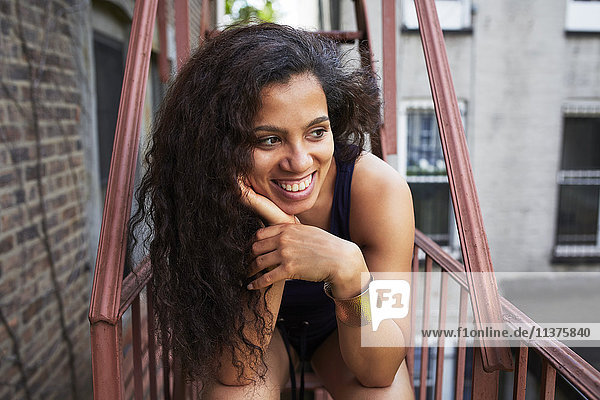 Portrait of smiling woman relaxing on urban fire escape