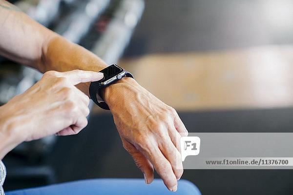 Caucasian woman tapping smart watch