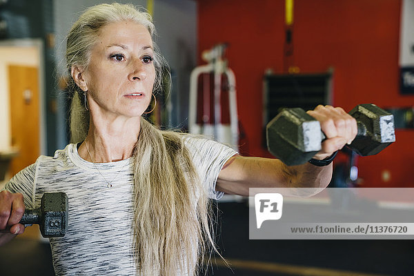 Caucasian woman lifting dumbbells in gymnasium