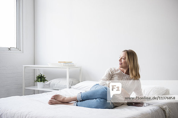 Caucasian woman laying on bed looking at window