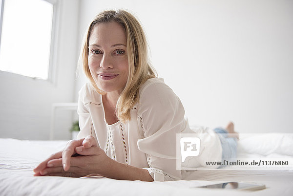 Portrait of smiling Caucasian woman laying on bed