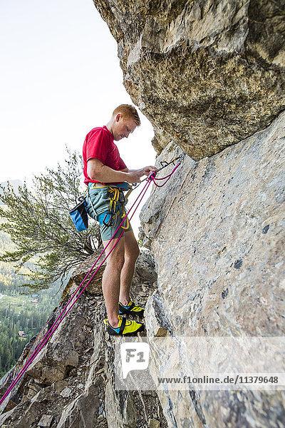 Caucasian man adjusting rope while rock climbing