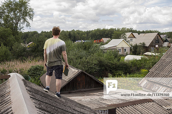 Caucasian man standing on roof holding book