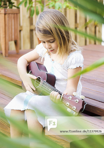 Caucasian girl sitting on patio playing ukulele