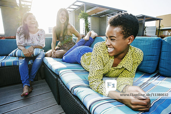 Friends laughing on rooftop sofa