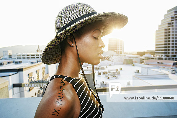Pensive Black woman wearing sun hat on rooftop