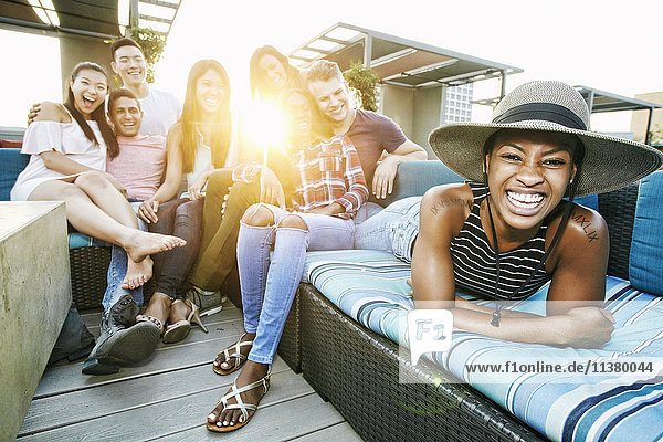 Portrait of smiling friends on rooftop sofa