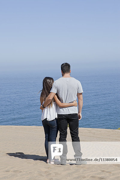 Hispanic couple admiring seascape at beach